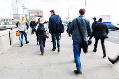 Commuters walking on the London Bridge in London, UK Royalty Free Stock Images
