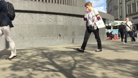 Commuters walking pass Kings Cross Square enroute to Kings Cross station stock footage