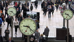 Commuters walking past clocks, Canary Wharf, London stock video footage