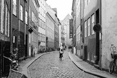 Commuting in Copenhagen by Bicycle. A cello player makes her way through the narrow cobblestone streets of Copenhagen on her bicycle Stock Photo
