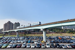 Commuting to the City. A shot of a Taipei MRT train crossing over a busy parking lot on the outskirts of the city between Muzha and Taipei Zoo Station Stock Photos