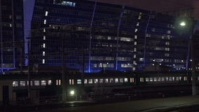 Commuting by train. Evening trip in the city. Commuter train passing by open platform in the city at night. Modern illuminated building in background stock video