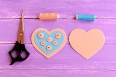 Como fazer ofícios de um coração de feltro etapa Em um lado do feltro o coração abotoa-se costurado usando a linha azul Tesouras, foto de stock