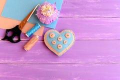 Como fazer ofícios de um coração de feltro etapa O coração decorativo de feltro, tesouras, linha, agulha, feltro cobre, almofada  fotografia de stock royalty free