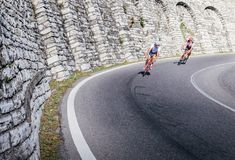 Two high-speed cyclists ride downhill on a curve in Como, Italy Stock Photos