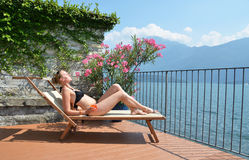 Como lake. Young woman sunbathing at the Como lake Stock Photography