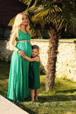 Como madre tenga gusto de la hija mujer embarazada hermosa con su niño fotografía de archivo