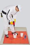 Como misturar o adesivo da telha na cubeta Imagens de Stock Royalty Free