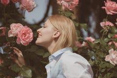 Como proposta quanto a flor Jovem mulher em florescer o arbusto cor-de-rosa O cheiro bonito da mulher aumentou flores no jardim d fotos de stock