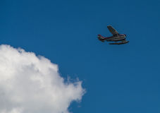 Como 11. Small aircraft flying across deep blue sky with fluffy white cloud foreground Royalty Free Stock Photography