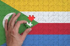 Comoros flag is depicted on a puzzle, which the man`s hand completes to fold.  stock illustration