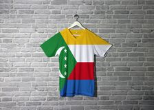 Comoros flag on shirt and hanging on the wall with brick pattern wallpaper royalty free stock photography