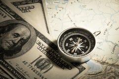 Compás con el dinero en mapa Fotografía de archivo