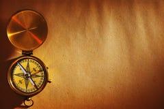 Compás de cobre amarillo antiguo sobre viejo fondo imagenes de archivo