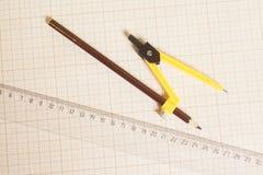 Compás de dibujo amarillo con el lápiz negro y regla en gráfico Imágenes de archivo libres de regalías