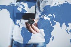 Compás de la mano del hombre con el mapa del mundo fotos de archivo