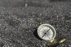 Compás de oro en la arena negra Foco en el compás foto de archivo