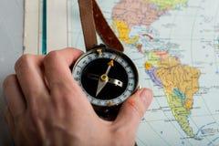 Compás a disposición contra la perspectiva de un mapa del mundo brillante foto de archivo libre de regalías