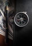 Compás en el libro con la pluma y el dinero Foto de archivo libre de regalías