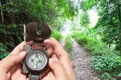 Compás en la mano, en fondo del bosque Imagen de archivo libre de regalías