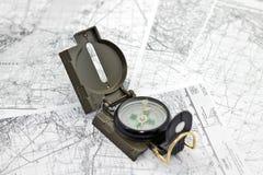 Compás en los mapas del fondo Imagenes de archivo