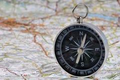 Compás en un mapa de camino foto de archivo libre de regalías