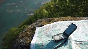 Compás moderno con el mapa de papel del terreno en la corriente ancha cercana de piedra resistida de la montaña metrajes
