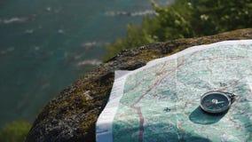 Compás redondo simple con el mapa de papel del terreno en la corriente ancha cercana de piedra resistida de la montaña almacen de metraje de vídeo