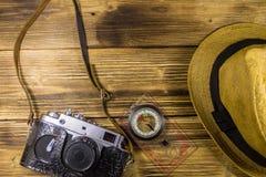 Compás, sombrero y cámara retra de la foto en fondo de madera Fotografía de archivo libre de regalías