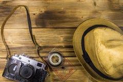 Compás, sombrero y cámara retra de la foto en fondo de madera Fotografía de archivo