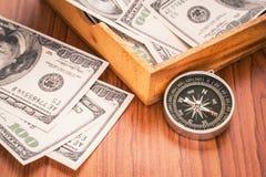 Compás y billetes de dólar Fotos de archivo libres de regalías