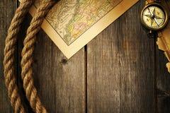 Compás y cuerda antiguos sobre mapa viejo Foto de archivo libre de regalías