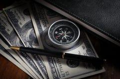 Compás y pluma en el dinero con el libro Fotografía de archivo