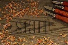 Compétence découpée en bois avec des burins images libres de droits