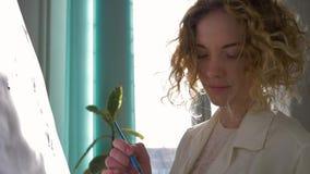 Compétence inspirée, femelle d'artisan d'artiste avec le pinceau appréciant peignant le tableau sur la toile à l'atelier dans nat clips vidéos