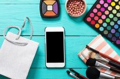 Compõe acessórios Vista superior Fundo de madeira azul Telefone celular com tela vazia Produtos cosméticos Imagens de Stock