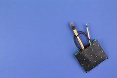 Compõe escovas com o saco de compras preto do papel do às bolinhas no fundo azul Fotografia de Stock