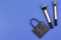 Compõe escovas com o saco de compras preto do papel do às bolinhas no fundo azul Foto de Stock Royalty Free