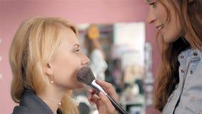 Compõe o artista que faz o profissional da jovem mulher, escova nas mãos do estilista Imagem de Stock Royalty Free