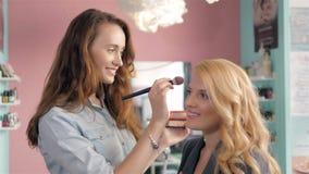 Compõe o artista que faz o profissional da jovem mulher, escova nas mãos do estilista Fotografia de Stock