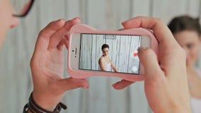 Compõe o artista que toma a foto de seu cliente com a composição e o penteado elegante vídeos de arquivo