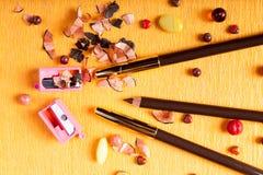 Compõe o lápis de olho do lápis com um apontador ao lado dele no fundo amarelo do papper Fotografia de Stock Royalty Free