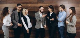 Compañía acertada con los trabajadores felices que se colocan en fila en oficina moderna fotografía de archivo