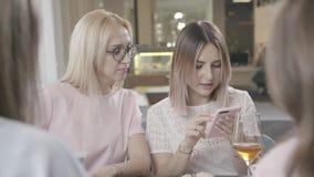 Compañía de amigos en un café y fotos de la demostración en el teléfono y la risa almacen de video