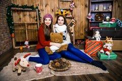 Compañía de dos muchachas con los regalos en el cuarto con las paredes de madera Imagenes de archivo