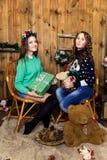 Compañía de dos muchachas con los regalos en el cuarto con las paredes de madera Imagen de archivo libre de regalías
