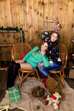 Compañía de dos muchachas con los regalos en el cuarto con las paredes de madera Foto de archivo