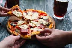 Compañía de los amigos que comen la pizza hecha en casa y que beben la cerveza oscura, imagenes de archivo