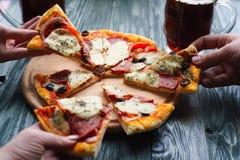 Compañía de los amigos que comen la pizza hecha en casa y que beben la cerveza oscura, fotografía de archivo