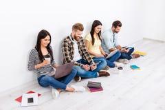 Compañía de los estudiantes felices que se sientan en el piso con las piernas cruzadas Foto de archivo
